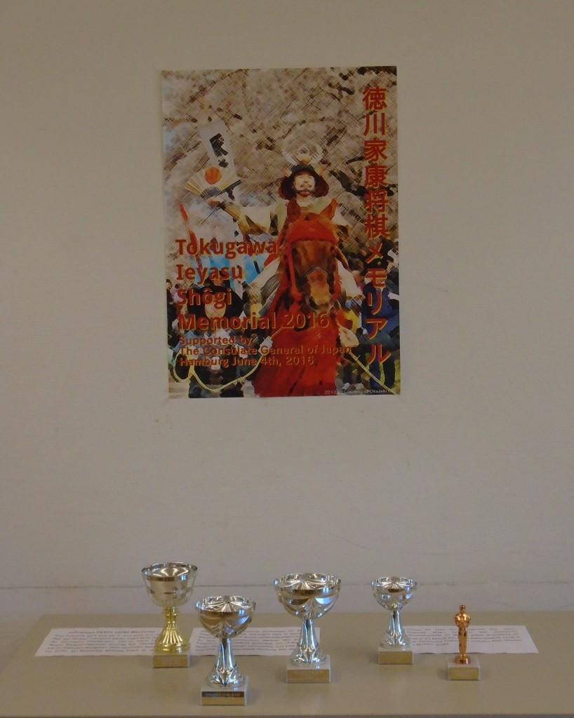 """Und der große General wachte über allem: Turnierplakat mit einem Tokugawa Ieyasu zu Pferd (basierend auf einem Foto, das aufgenommen worden war während einer LARP-Parade mit Laiendarstellern im April 2013 in Okazaki, der Geburtsstadt des Shogun; Produktion des Plakats: Fabian Krahe) über den Pokalen, die vom Japanischen Generalkonsulat in Hamburg gestiftet worden waren für das """"Tokugawa Ieyasu Shogi Memorial 2016"""". Foto: Rolf Müller"""