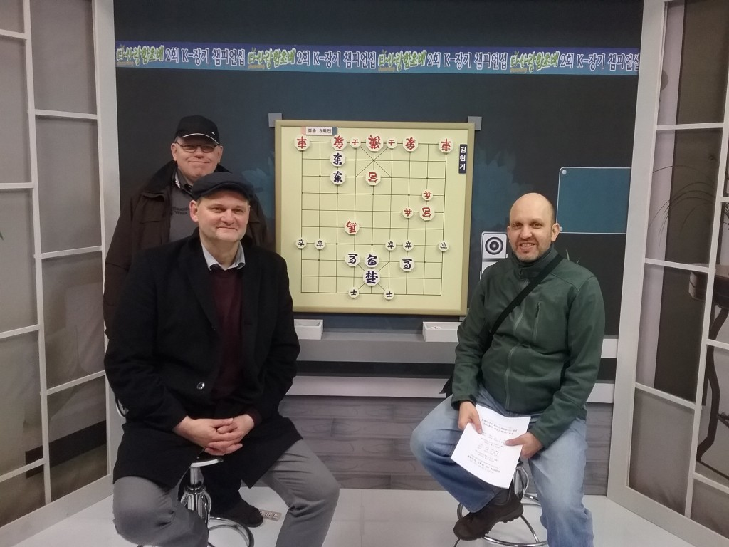 Das Bild zeigt die Hamburger Janggi-Aktivisten Uwe Frischmuth (vorne links), Jürgen Woscidlo (hinten links) und Martin Wolff (rechts), die zusammen die deutsche Delegation gebildet haben, im Brain TV-Studio bei der Janggi-WM im November 2017 in Seoul.