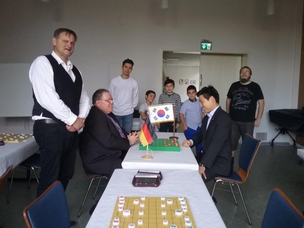 Gleich wird an der Pforte des gegnerischen Palasts gerüttelt: Shin-Gyu Kang, Präsident der Deutsch-Koreanischen Gesellschaft Hamburg (rechts am Brett), und Turnierdirektor Jürgen Woscidlo (li.) eröffnen mit dem symbolischen ersten Zug das 2. Internationale Janggi-Open am 13. Oktober 2018 in der Hansestadt. Und auch Deutschlands Janggi-Spitzenspieler Uwe Frischmuth (vorne links) hat sich voller Tatendrang für einen spannenden Wettkampf in Position gebracht … während vordergründig bescheiden in der letzten Reihe schon der spätere Turniersieger Krzysztof Stoigniew Sieja wartet … (ganz hinten rechts).