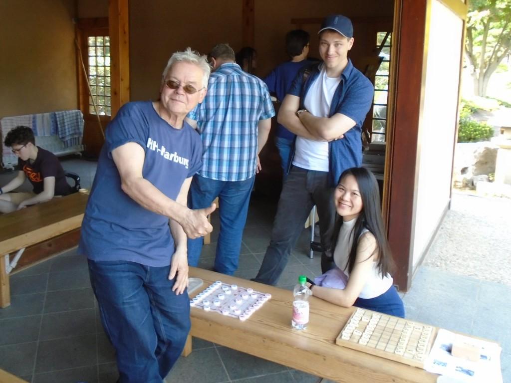 Spaß beim Mattsetzen nach jenem Regelwerk, das schon Chinas hochverehrter Kong Fu Zi aka Meister Konfuzius (ca. 551 - 479 v. Chr.) empfohlen hat: Liang Peiyun (vorne rechts) mit René Gralla (li. stehend) und Xiangqi-Brett (links neben Liang Peiyun auf der Bank). Foto: Rolf Müller.
